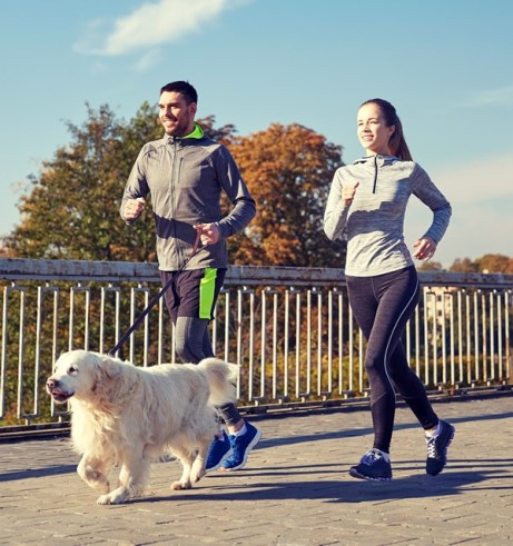 happy-couple-with-dog-running-outdoors-P3HP888
